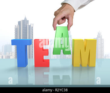 Putting A in for TEAM on glass table in office - Stock Photo