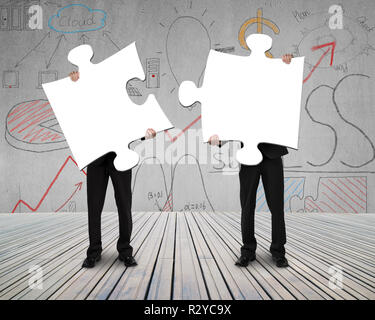 Two people holding puzzles to connect business doodles background - Stock Photo