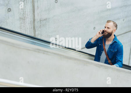 Bearded man using his mobile phone on an ascending escalator with copy space ahead of him - Stock Photo