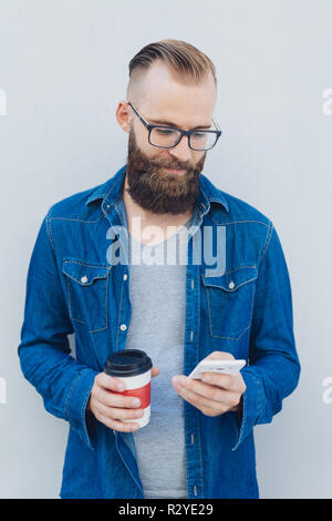 Man in denim jacket wearing glasses holding takeaway coffee texting on his mobile phone - Stock Photo