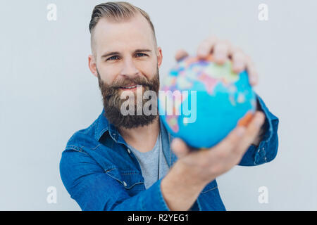 Portrait of young cheerful bearded man holding globe - Stock Photo