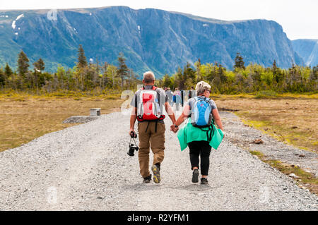 People walking along track to start of Western Brook Pond in Gros Morne National Park, Newfoundland. Group heading to boat trip. - Stock Photo