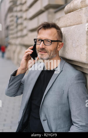 A mature professional, metro man with glasses talking on a smart phone in an urban street scene. - Stock Photo