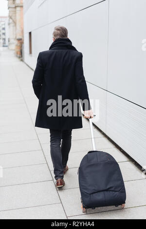 Rear view of mature man wearing black coat pulling suitcase along pavement - Stock Photo