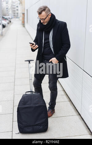 Mature man wearing black coat using mobile phone while standing with suitcase on sidewalk - Stock Photo