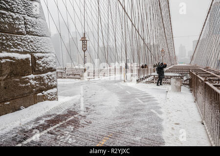 Brooklyn Bridge at snow storm, a view to Manhattan buildings in fog