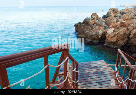 Image of a wooden brown pier with ropes near amazing blue sea water near rocks on the background of many boats on a cloudless fall day. Cyprus, Konnos - Stock Photo