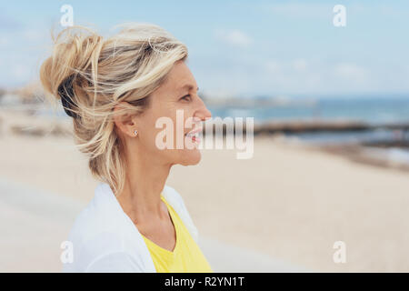 Attractive serious blond woman profile portrait as she stands on a sandy beach looking out over the ocean with a thoughtful expression - Stock Photo
