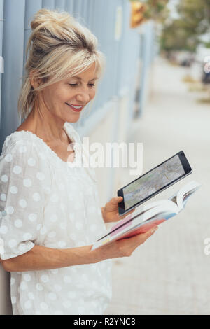 Elderly attractive woman tourist sightseeing standing in an urban street holding a guide book and tablet - Stock Photo