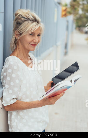 Elderly female tourist using a guide book and tablet pc to research places of interest as she stands in an urban street - Stock Photo