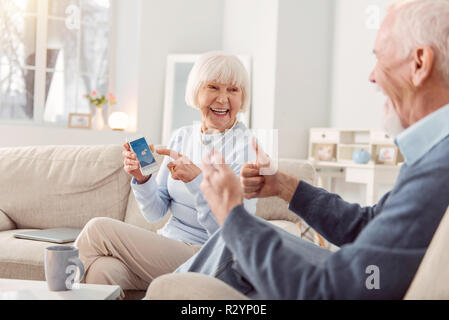 Woman wearing a blue sweater showing weather forecast to her husband - Stock Photo