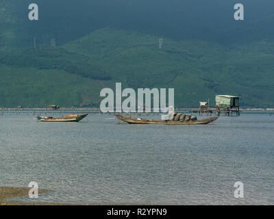 Fishing boats and shed  moored in Lang Co village lagoon South Vietnam between Lap An Lagoon and South China Sea known for seafood - Stock Photo