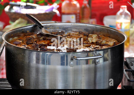 Stew in metal pot on plaid tablecloth. Balkan traditional food - Stock Photo