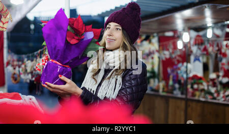 Portrait of young woman customer choosing floral decorations for Christmas outdoor - Stock Photo