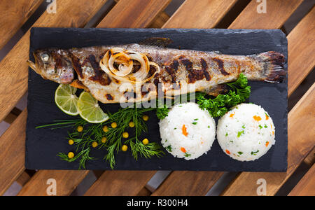 Top view of baked whole trout with rice, grilled onions, greens, canned peas and lime on black serving board - Stock Photo