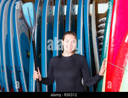 Young woman surf club instructor wearing water suit, standing next to paddle boards - Stock Photo