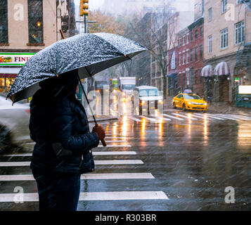 A woman waits to cross Eighth Avenue in the Chelsea neighborhood of New York during the first snow of the season on Thursday, November 15, 2018. A coating to an inch of slushy snow is expected in the city before it turns to rain in the evening. (© Richard B. Levine) - Stock Photo
