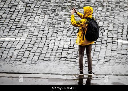 Tourist in the rain on Red Square, Moscow, Russia. Man wearing yellow rain coat with hood up and rucksack taking a photograph. - Stock Photo