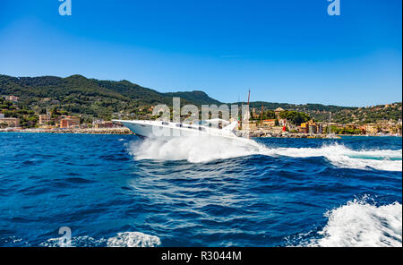 Santa Margherita, Cinque Terre, Liguria, Italy - August 11, 2018 - View of a small yacht sailing on the sea in front of the city - Stock Photo