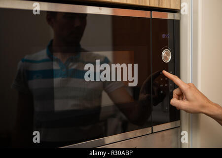 Photo of microwave oven and man's hand in kitchen - Stock Photo