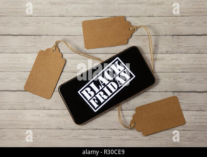 Price tags and phone with the inscription black friday on a wooden background, the concept of sales - Stock Photo