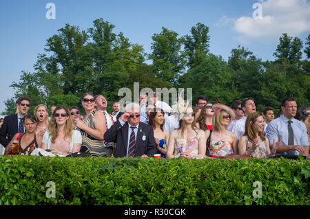 Excitement as a race passes Remenham Club at Henley Royal Regatta, Henley-on-Thames, Oxfordshire - Stock Photo