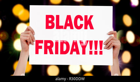 Black Friday! Female hands holding a placard with abstract lights bokeh background. Commercial appeal concept - Stock Photo
