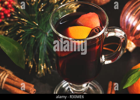Christmas hot mulled wine in a glass mug with orange spices and fruit close-up. Selective focus. - Stock Photo