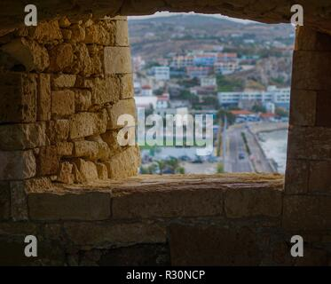 View from Venetian Fortress of Rethimno overlooking the town through a window in the stone wall. Rethimno, Crete. - Stock Photo