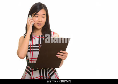 Young beautiful Asian businesswoman reading clipboard while talk - Stock Photo