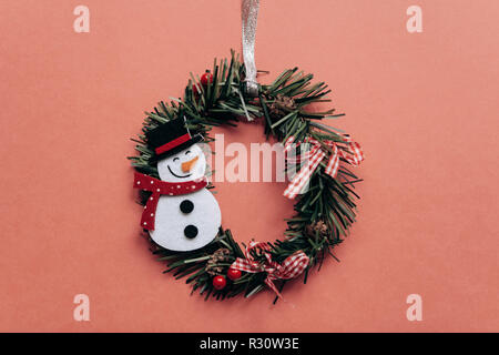 Christmas wreath with snowman Christmas tree toy on red background creative festive idea in minimalist style. Minimalism - Stock Photo