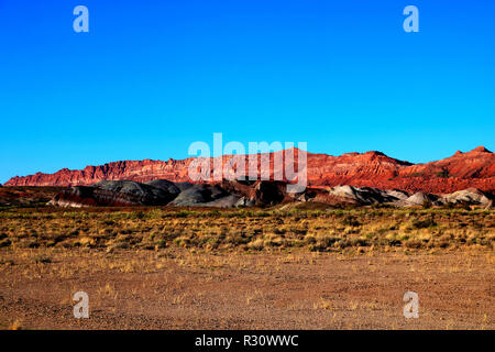 After a raw, gray day of wind-blown showers and flurries, the afternoon sky cleared and shone a beautiful light on the hills by Blue Mesa, in Painted  - Stock Photo