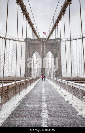Couple walking over Brooklyn Bridge at heawy snow storm - Stock Photo