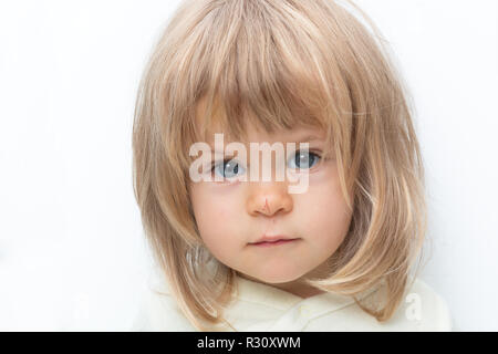 Blue-eyed blond baby with Bob hair and scratched nose close-up. Isolated on white. Female child looking seriously at camera in white studio, frowning eyebrows. Negative emotions, displeasure, offence. - Stock Photo