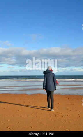 Young woman dressed for the cold, walking on the beach towards the sea in winter. uk - Stock Photo