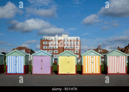 Brighton seafront five beach huts, with multi coloured doors of yellow, pink, black stripes behind is an appartment building and blue sky - Stock Photo