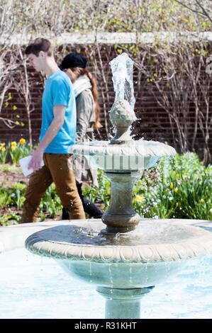 A young couple walking past a decorative water fountain. - Stock Photo