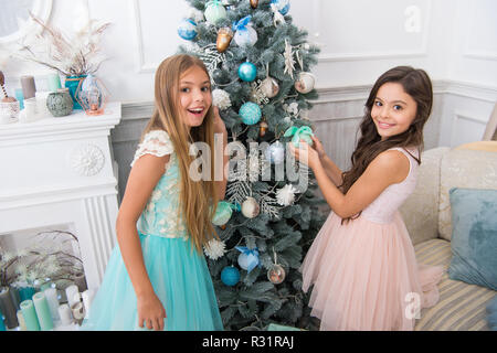 Sisters decorating tree. Cherished holiday activity. Kids fashionable dresses decorating christmas tree. Family tradition concept. Girls decorating christmas tree together. Siblings busy decorating. - Stock Photo