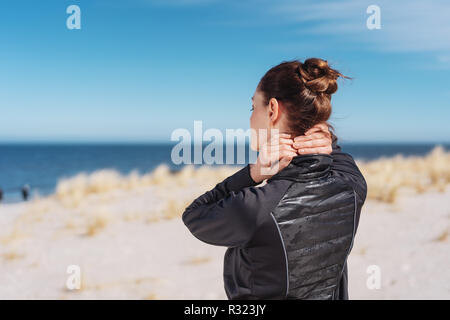 Woman with her hair in a neat bun walking on a beach rubbing her neck with both hands as she heads away from the camera towards the sea - Stock Photo