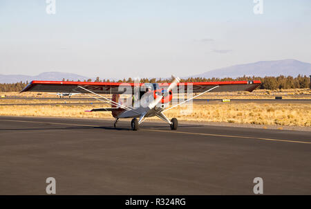A pilot takes off from a small airport in Bend, Oregon, in his 1997 Aviat Husky airplane. - Stock Photo