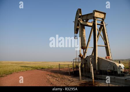 Crude oil production, pump jack, blue sky an fieds at sunset in the Niobrara shale, Wyoming, with copy space. - Stock Photo