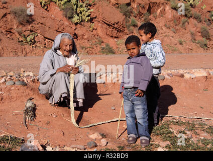 MARRAKESH, MOROCCO - 21,02,2012: An elderly, typically dressed Berber man with his grandchildren crafts straps from straw in the High Atlas Mountains. - Stock Photo