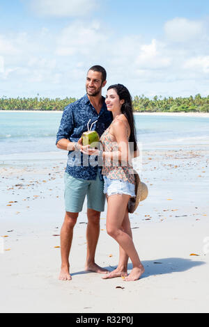 An attractive young couple in love on an idyllic beach in the tropics - Stock Photo