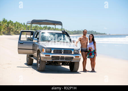 An attractive young couple with an off-road vehicle on a white sand beach - Stock Photo