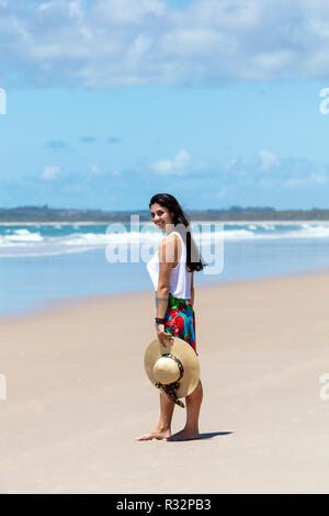 A beautiful young woman in a skirt, white top and straw hat on a white sand palm tree beach in the tropics