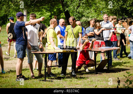 Komsomolsk-on-Amur, Russia - August 1, 2016. Public open Railroader's day. man shows his neighbor how to shoot sports pistol at amateur competitions - Stock Photo