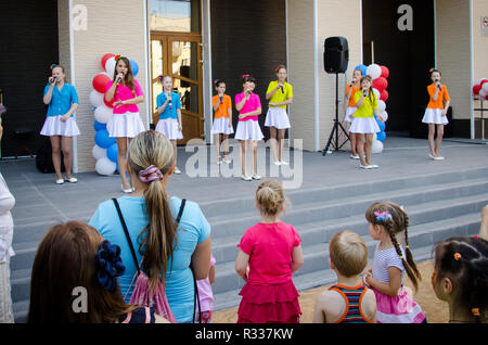 Komsomolsk-on-Amur, Russia - August 1, 2016. Public open Railroader's day. girls in colorful costumes sing and dance at city festival - Stock Photo