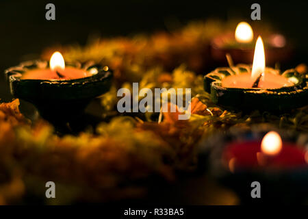 Lit diyas placed on flowers for celebrating diwali and dhanteras in Asia - Stock Photo