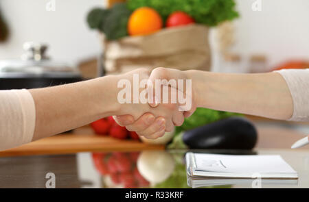 Close-up of human handshake. Two women in kitchen shaking hands to each other. Cooking, friendship or family fun concepts - Stock Photo