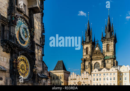 'Prazsky orloj', the astronomical clock of Prague's town hall, with the towers of 'Tynsky chram', the Tyn Church, in the background - Stock Photo